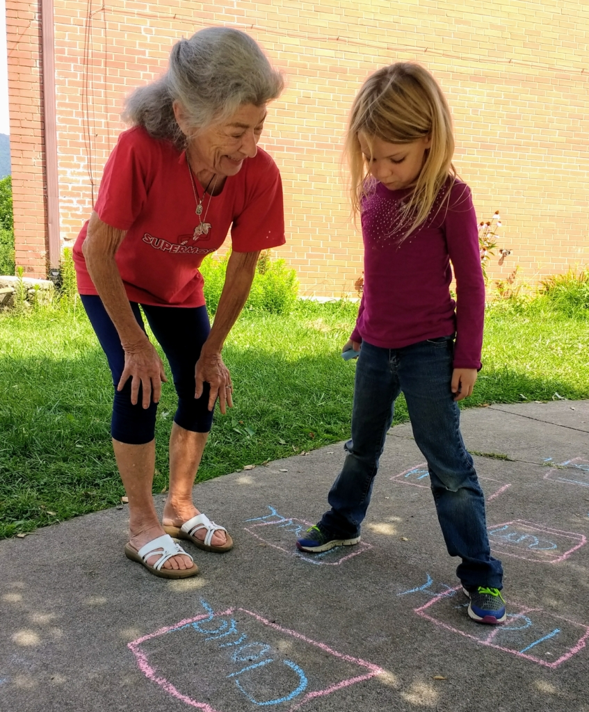 Volunteer Jeanne Theodore plays sight word hopscotch with a student in the Summer Enrichment Program.